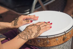 Women's hands decorated with traditional Indian painting on the drum Stock Image