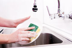 Women's hands in the dish sink. Royalty Free Stock Photo