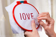 Women's hands embroider a word love Stock Photography