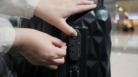 Women`s hands fasten the combination lock on the suitcase in airport. Woman fastens the combination lock on the suitcase in airport. She is preparing to flight stock footage
