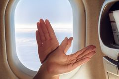 Women`s hands folded into the shape of a bird while in the cabin in front of the fuselage royalty free stock photos