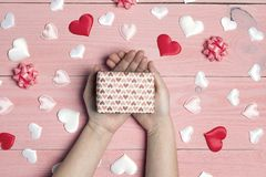Women`s hands with gift box surrounded by hearts on pink wooden background. Top-down romantic festive composition royalty free stock images