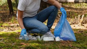Women`s hands in gloves close - up put garbage in a biodegradable bag. Woman volunteer collects garbage, taking care of