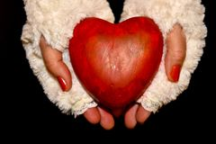 Women`s hands hold a big red heart as a symbol of love. Women`s hands, dressed in white fur gloves, hold a big red heart as a symbol of love royalty free stock photo