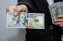 Women`s hands hold dollars. Close-up. Hand shows hundred dollar bill. stock image