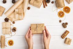 Women`s hands hold a gift of craft paper. Against the background of dried orange, cinnamon, pine cones, anise on a white table. Women`s hands hold gift of craft stock images