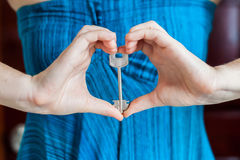 Women`s hands hold house key in the form of heart on the background of a wooden door. Owning real estate concept Stock Image