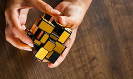 Women`s hands hold mirror magic cube on wooden background Royalty Free Stock Photos