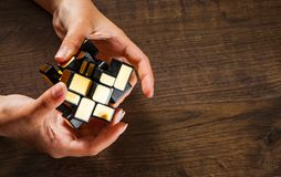 Women`s hands hold mirror magic cube on wooden background Royalty Free Stock Photo