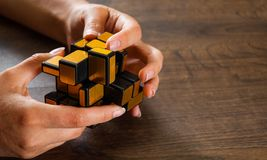 Women`s hands hold mirror magic cube on wooden background Royalty Free Stock Images