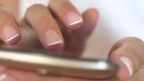 Women`s hands hold the smartphone and browser the website and email. close-up. A girl`s hand is typing a mobile message. Women`s hands hold the smartphone and stock footage