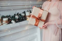 Women`s Hands Holding A Gift In Kraft Paper. Christmas Concept Royalty Free Stock Photography