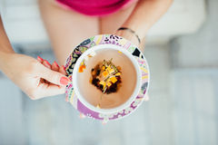 Women's hands holding a colorful cup of tea Stock Photos