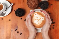 Women`s hands holding a Cup of coffee with a painted Teddy bear latte art. Vintage color. Coffee shop concept.  royalty free stock image