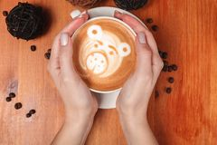 Women`s hands holding a Cup of coffee with a painted Teddy bear latte art. Vintage color. Coffee shop concept.  royalty free stock photo