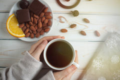 Women`s hands holding a cup of coffee on a wooden table. top view. Women`s hands holding a cup of coffee on a wooden table. top view royalty free stock photos
