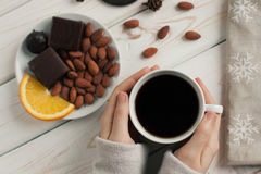 Women`s hands holding a cup of coffee on a wooden table. top view. Women`s hands holding a cup of coffee on a wooden table. top view royalty free stock photography