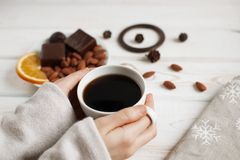 Women`s hands holding a cup of coffee on a wooden table. top view. Royalty Free Stock Photos