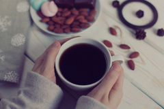 Women`s hands holding a cup of coffee on a wooden table. top view. Stock Images