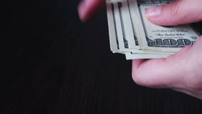 Women`s hands holding a fan of hundred dollar bills and counts. Women`s hands holding a fan of hundred dollar bills, and counts to a black wooden background stock footage