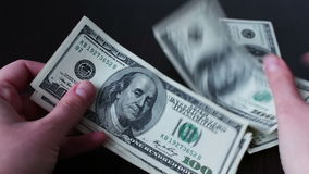 Women`s hands holding a fan of hundred dollar bills and counts stock video footage
