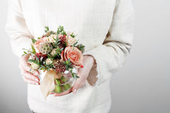Women`s hands, holding glass vase with forest spring flower bouquet, close up Stock Photo