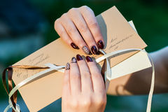 Women's hands holding mail envelope. Beautiful hand of a young woman with brown manicure holding an mail envelope Royalty Free Stock Images