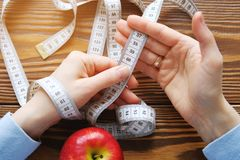 Women`s hands holding a measuring tape on a wooden background. Red Apple down . Close up. The concept of diet, healthy lifestyle royalty free stock photography