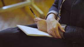 Women`s hands holding a pen and a notebook. Close up of female hands holding a pen and a notebook stock video