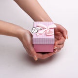 Women's hands holding a pink gift with a note I love you. Stock Photo