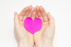 Women's hands holding a pink heart. Made of paper Stock Images