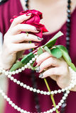 Women's hands holding rose, pearl. Beautiful hand of a young woman with brown manicure holding red rose white pearl necklace stock photography