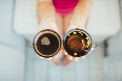 Women's hands holding tea and coffee Royalty Free Stock Photography