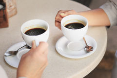 Women's hands are holding white cups with coffee. Stock Image