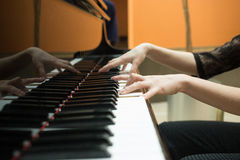 Women's hands on the keyboard of piano. girl plays Stock Photos