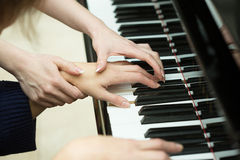 Women's hands on the keyboard of piano. girl plays Royalty Free Stock Image
