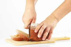 Women's hands with a knife sliced rye bread. On a cutting board close up Stock Photo