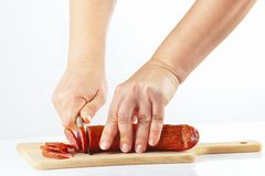 Women's hands with knife sliced salami on cutting board Royalty Free Stock Image