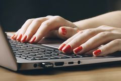 Women`s hands on the laptop keyboard, passport, smartphone, camera and map. royalty free stock photo