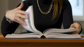 Women`s hands leafing through a book. Woman sitting at the table leafing through the book. 4K stock footage