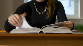 Women`s hands leafing through a book. Woman sitting at the table leafing through the book stock video