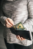 In the women`s hands is the leather wallet with a wad of hundred dollars. Business offer. Beautiful manicure Stock Photography