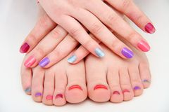 Women's hands and legs with a colored nails Royalty Free Stock Photography