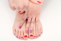 Women's hands and legs with a colored nails Royalty Free Stock Photo