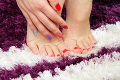 Women's hands and legs with a colored nails Royalty Free Stock Photos
