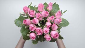 Bouquet of roses. 9. Women`s hands locate a bouquet of pink roses on the table. Slow motion. 9 stock video footage