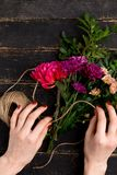 Bouquet of flowers in female hand on a black wooden table royalty free stock photo