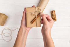 Women`s hands making a gift from craft paper. stock image