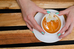 Women's hands with mug of green tea and jasmine flower on the background of wooden planks, top view Stock Photo