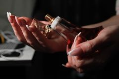 Women`s hands with nail arts on nails holding bottle of perfume stock photo